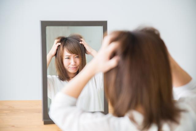 鏡の前でパサパサ髪に悩む女性
