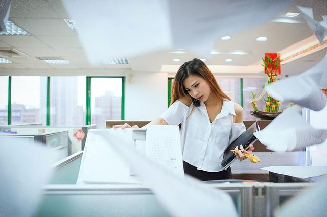コピー機の前で忙しさのあまり書類を散らばらせる女性